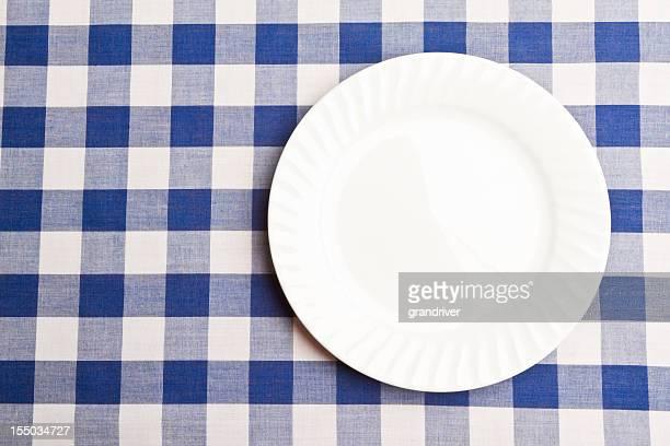 Plaque blanche sur nappe à carreaux bleus