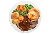 Traditional Sunday roast dinner with roast beef, yorkshire pudding and vegetables