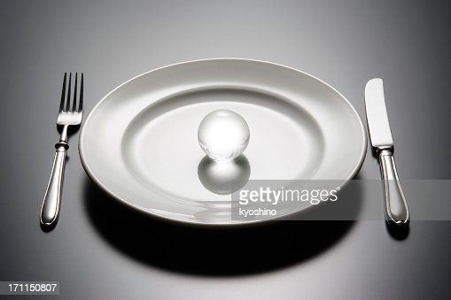 White plate with shining crystal ball on black table