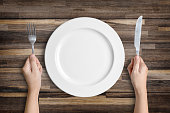 Dinner place setting. A white plate with silver fork and spoon isolated on wood background with clipping path