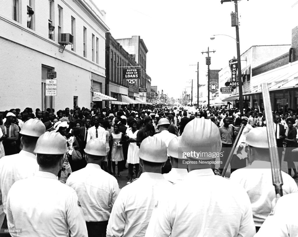 White policemen wear hardhats and carry doublebarrelled shotguns as they block mourners demonstrating at the funeral of slain civil rights activist...
