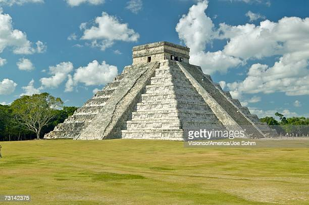 White puffy clouds over the Mayan Pyramid of Kukulkan (also known as El Castillo) and ruins at Chichen Itza, Yucatan Peninsula, Mexico