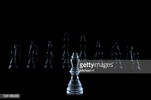 White queen facing black chess pieces
