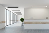 White reception desk with a wooden stripe is standing in a white office lobby with a row of doors, potted trees and a concrete floor with loft windows. Close up. 3d rendering mock up