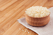 White rice basmati in wooden bowl on brown bamboo board, closeup. Rustic style, healthy dietary cereals  background.