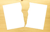 White Ripped Paper in Half on Wood Background. White torn paper 2 part for separate or partition or divide concept