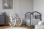 White rocking chair with pillow next to wooden cradle in elegant baby room with duck's poster on the wall