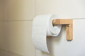 A white roll of soft toilet paper neatly hanging on a modern wooden holder on a white tile bathroom wall.