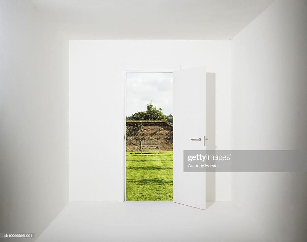 White room with walled garden seen through open door (Digital Composite) : Stock Photo