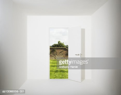 White room with walled garden seen through open door (Digital Composite) : Stock Photo