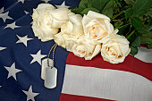 Military dog tags and white rose bouquet on American flag.