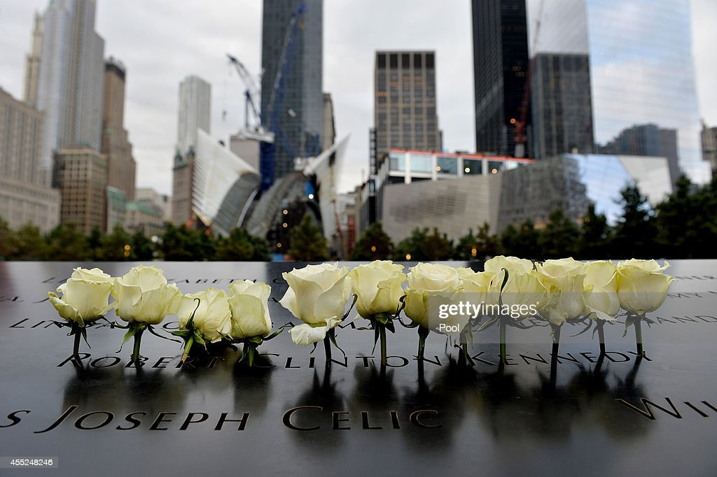 White roses are placed in an inscribed name along the edge of the North Pool during memorial observances held at the site of the World Trade Center...