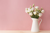 White blooming roses placed in vintage vase on soft pink background.