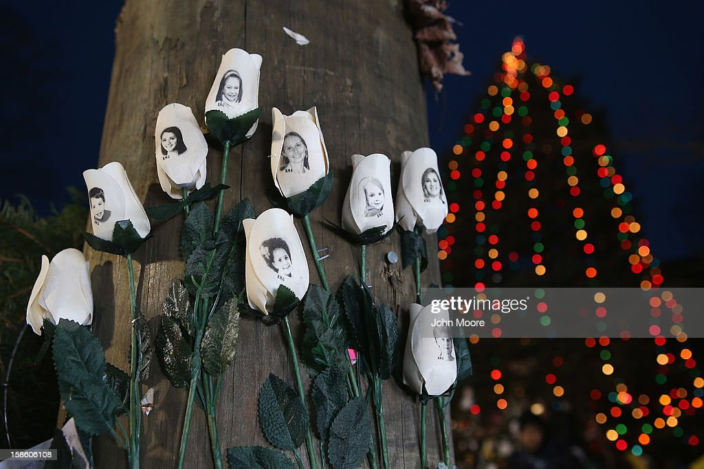 White roses with photos of people killed in last Friday's massacre hang at a streetside memorial on December 20, 2012 in Newtown, Connecticut. Six funeral services were held Thursday in the Newtown area for students and teachers slain in the attack.