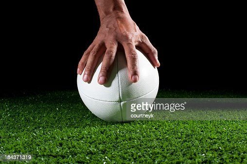 White rugby ball with hand holding it in grass