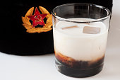 A White Russian (Kahlua, Vodka and Half & Half) on the rocks with a Russian ushanka hat (with a hammer and sickle medalian) on a white background.