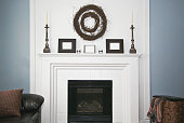 White fireplace with wooden rustic decorations. Grapevine Double Wreath on wall.