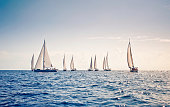 Sailing ship yachts with white sails at the open sea