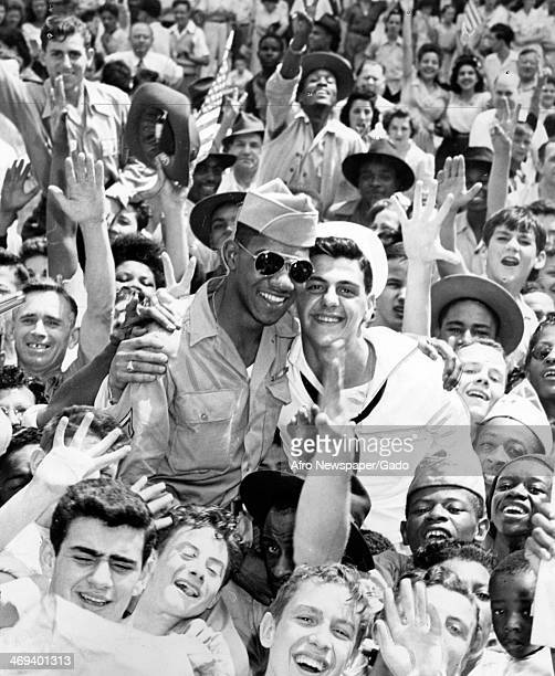A white soldier and an African American soldier hug while being lifted onto the shoulders of a mixed race crowd on VJ Day following the victory over...