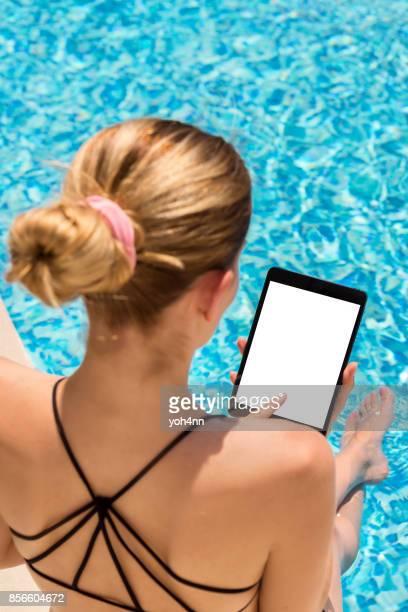 Tableta de la pantalla blanca y la mujer en piscina