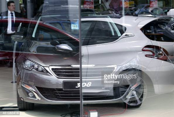 A white secondhand automobile right is reflected in a window as a new Peugeot 308 automobile produced by PSA Peugeot Citroen left sits inside Toomey...