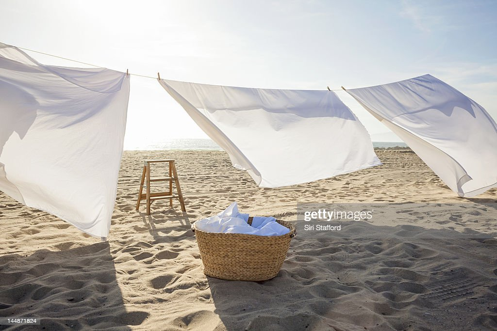 White Sheets hanging on laundry line at beach : Stock Photo