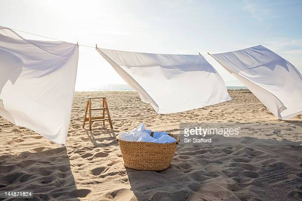 White Sheets hanging on laundry line at beach