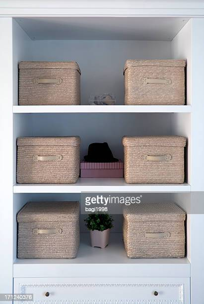 White shelved with tan boxes atop them