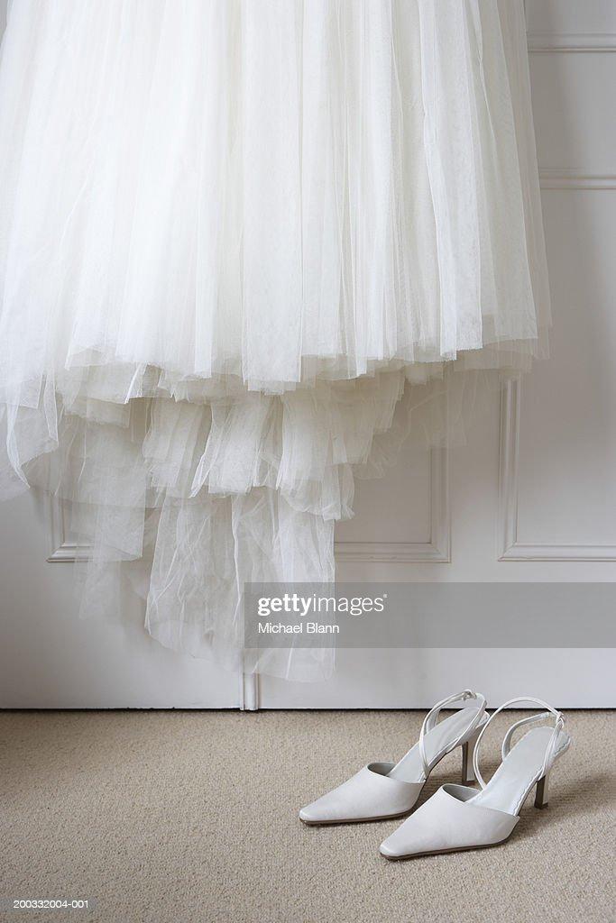 White shoes on floor beneath wedding dress hanging outside wardrobe