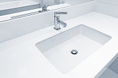 White sink by the mirror in the bathroom.