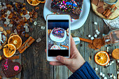 White smartphone in a woman's hand takes a piece of cake and sweets, view from the top