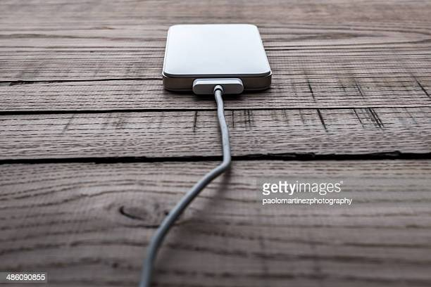 White smartphone in charge on wooden table