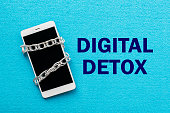 White smartphone with metal chain on blue background. Digital detox, dependency on tech, no gadget and devices concept