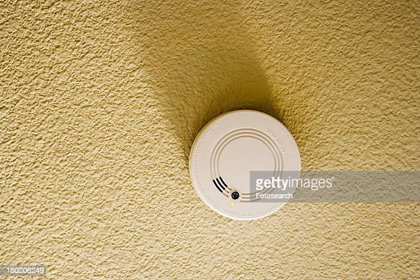 White smoke detector on yellow ceiling