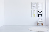 Copy space of white spacious autistic kid's room with drawings white cabinet and carpet