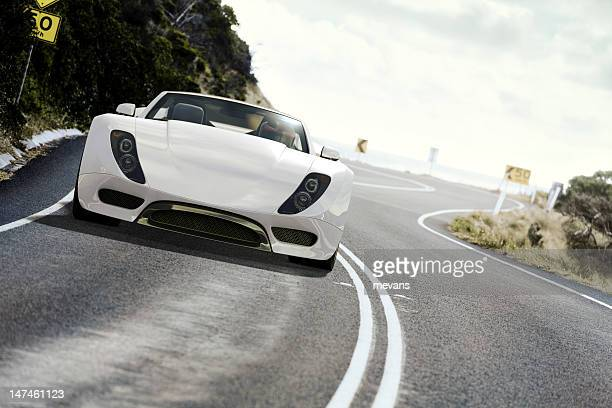 White sports car on coastal road at daytime