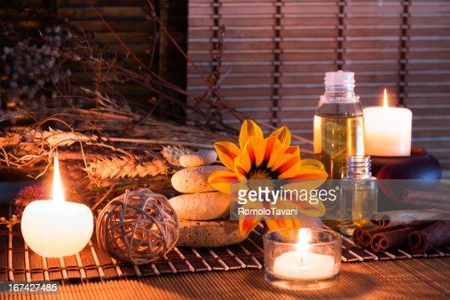 Pedras brancas flores secas, velas, óleo, no tapete : Foto de stock