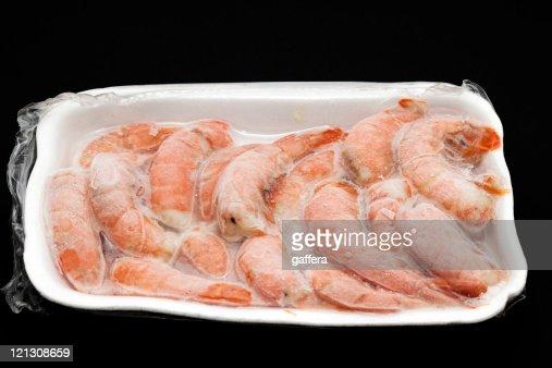 A white Styrofoam tray full of frozen shrimp