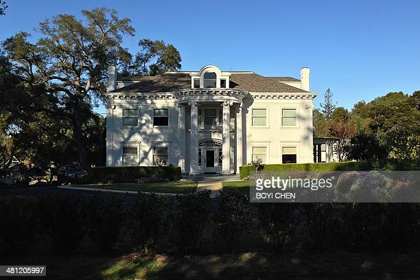 White Suburban House in Saratoga California with huge columns in the front porch and mature trees in the surrounding area