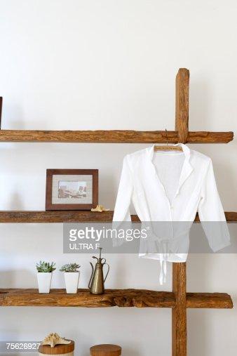 White summer shirt hanging on clothes hanger on natural wooden shelves