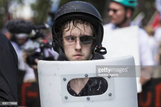 A White Supremacists with one lens knocked out of his sunglasses holds up a shield during clashes with counter protestors at Emancipation Park where...