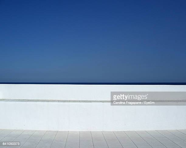 White Surrounding Wall Against Clear Blue Sky On Sunny Day