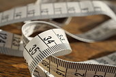 White tape measure (tape measuring length in meters and centimeters) on the wooden surface as symbol of tool used by tailor and people reducing weight during