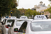 White taxi cars parking along the footpath in Adelaide, Australia with blurred background