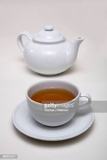 White teapot and tea cup filled with green tea