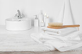 White towels on wooden table over blurred simple bathroom background