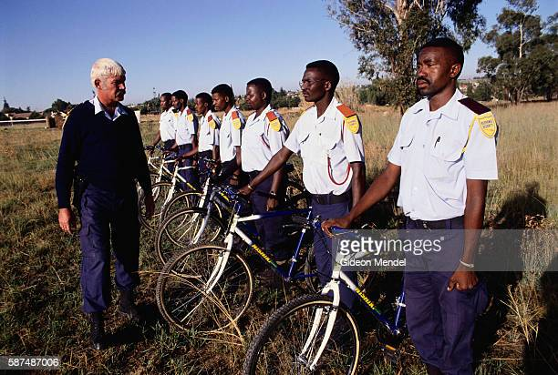 A white training officer speaks with a group of black bicycle security guards during a training exercise in a field in South Africa