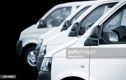 White transporters / vans in a row on black background