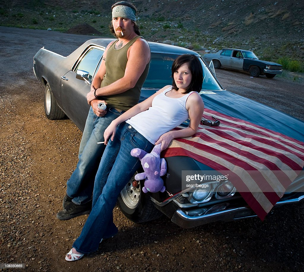 White trash patriots leaning against car