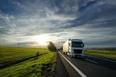 White truck driving on asphalt road between fields and meadows in rural landscape at sunset